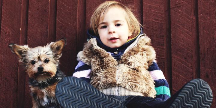 Little boy sitting beside his puppy